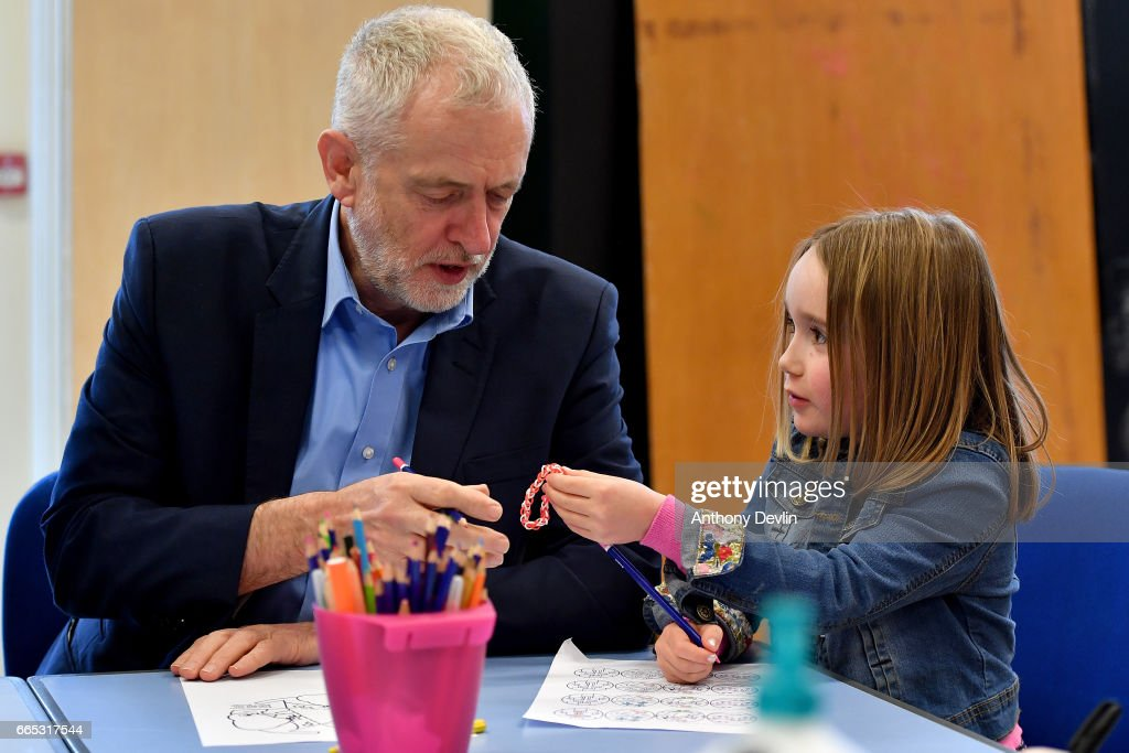 Leader of the Labour Party Jeremy Corbyn MP is given a loom band by Zofia Bylinski-Gelded, 7, during a visit to a children's holiday club in Leyand where he made an education policy announcement on April 6, 2017 in Leyland, England. The Leyland Project provides services to the community, including after School provisions, lunch clubs and youth clubs. The project uses cookery as an activity for families who rely on free school meals in term times as it becomes a struggle to cover the extra cost in the holidays.