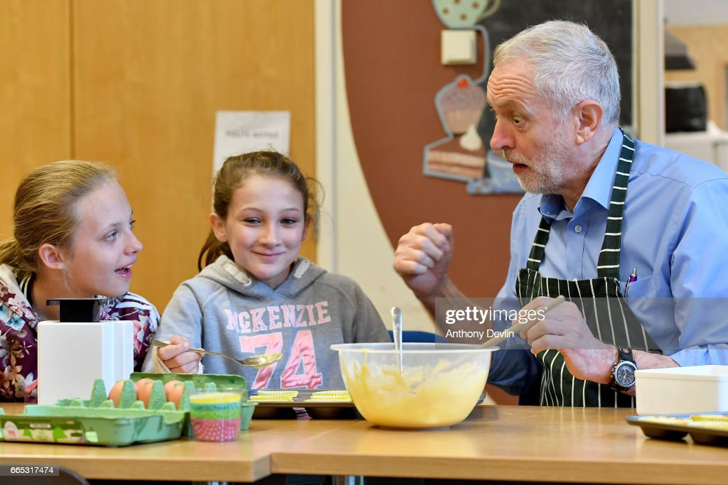 Leader of the Labour Party Jeremy Corbyn MP looks surprised as he makes fairy cakes with Lilly Cox (L) and McKenzie Fitzgerald during a visit to a children's holiday club in Leyand where he made an education policy announcement on April 6, 2017 in Leyland, England. The Leyland Project provides services to the community, including after School provisions, lunch clubs and youth clubs. The project uses cookery as an activity for families who rely on free school meals in term times as it becomes a struggle to cover the extra cost in the holidays.