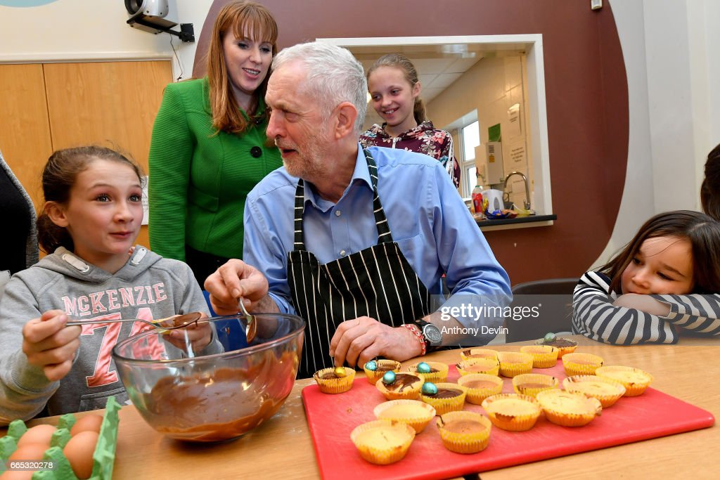 Leader of the Labour Party Jeremy Corbyn MP makes fairy cakes with McKenzie Fitzgerald (L) Shadow Secretary for Education Angela Rayner (2nd L) and Lyra Bylinski (R) during a visit to a children's holiday club in Leyand where he made an education policy announcement. April 6, 2017 in Leyland, England. The Leyland Project provides services to the community, including after School provisions, lunch clubs and youth clubs. The project uses cookery as an activity for families who rely on free school meals in term times as it becomes a struggle to cover the extra cost in the holidays.
