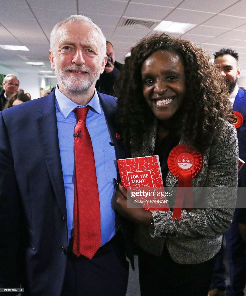 Leader of the Labour party Jeremy Corbyn poses for a photograph with Labour's Parliamentary Candidate for Edmonton, Kate Osamor (R) after making a speech, at Peterborough Football Club in Peterborough, central England on May 19, 2017, as campaigning continues in the build up to the general election on June 8. / AFP PHOTO / Lindsey Parnaby