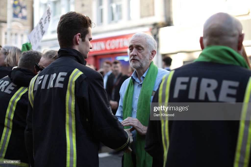 Leader of the Labour Party, Jeremy Corbyn shakes hands with firefighters during a silent march on the one year anniversary of the Grenfell Tower fire on June 14, 2018 in London, England. In one of Britain's worst urban tragedies since World War II, a devastating fire broke out in the 24-storey Grenfell Tower on June 14, 2017 where 72 people died from the blaze in the public housing building of North Kensington area of London.