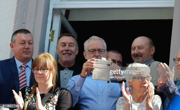 Leader of the Labour Party Jeremy Corbyn takes a photograph with his phone as he watches colliery bands pass below the County Hotel balcony during...
