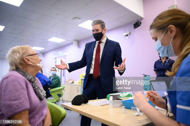 Leader of the Labour Party Keir Starmer chats with Ruby Byers before she receives the first of two vaccination shots at the NHS vaccination centre in...