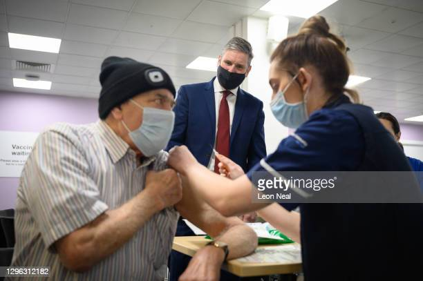 Leader of the Labour Party Keir Starmer looks on as Melvin Allanson receives the first of two vaccination shots at the NHS vaccination centre in...