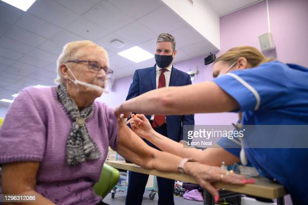 Leader of the Labour Party Keir Starmer looks on as Ruby Byers receives the first of two vaccination shots at the NHS vaccination centre in Robertson...