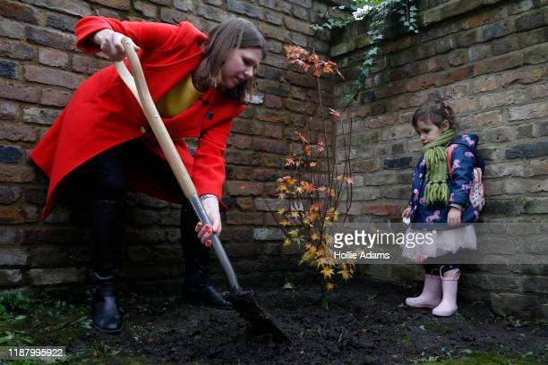 Leader of the Liberal Democrats Jo Swinson plants a tree at Razumovsky Academy in Kensal Green as 25 yr old Maya Litani watches on November 16 2019...