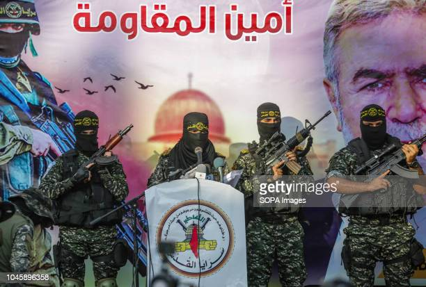 Leader of the military group gave a speech on stage Members of the Palestinian AlQuds Brigades the military wing of the Islamic Jihad group march in...