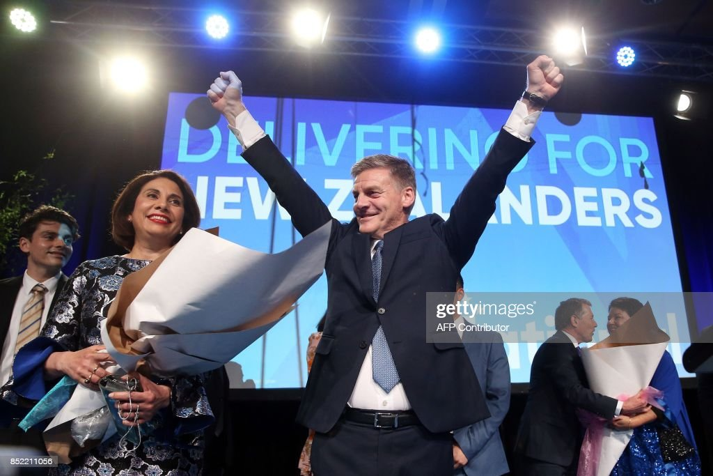 Leader of the National Party Bill English (C) gestures next to his wife Mary (L) onstage at the party's election event at SkyCity Convention Centre in Auckland on September 23, 2017. New Zealanders went to the polls on September 23 to elect a new parliament. /