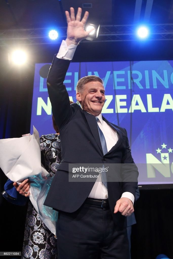 Leader of the National Party Bill English waves to supporters onstage at the party's election event at SkyCity Convention Centre in Auckland on September 23, 2017. New Zealanders went to the polls on September 23 to elect a new parliament. /