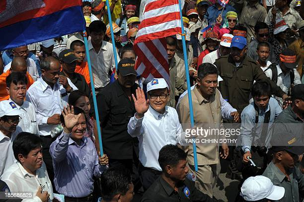 Leader of the opposition Cambodia National Rescue Party Sam Rainsy holds a US flag as he leads supporters during a demonstration in Phnom Penh on...