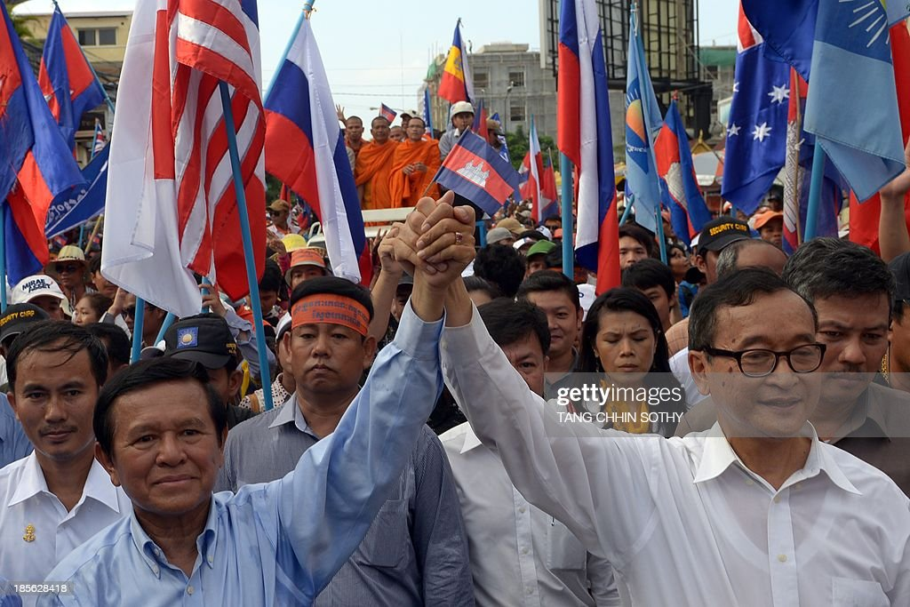 Leader of the opposition Cambodia National Rescue Party (CNRP) Sam Rainsy (R) and deputy of CNRP Kem Sokha (L) raise their hands as they march during a demonstration in Phnom Penh on October 23, 2013. Thousands of Cambodia opposition supporters staged a demonstration amid high security on October 23, over fiercely disputed elections that extended strongman Prime Minister Hun Sen's nearly three-decade rule, following bloody protests last month.
