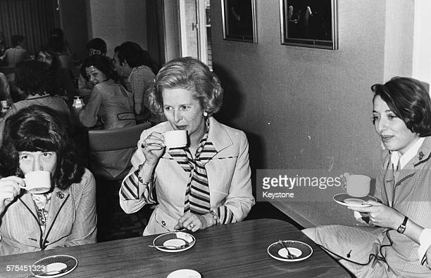 Leader of the Opposition Margaret Thatcher drinking a cup of tea with two sales girls during a visit to the Marks and Spencer department store in...
