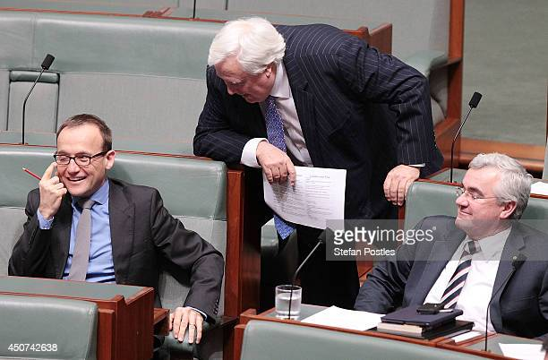 Leader of the Palmer United Party Clive Palmer speaks with Adam Bandt during the house of representatives Question time on June 17 2014 in Canberra...