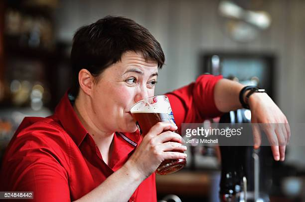 Leader of the Scottish Conservatives Ruth Davidson poses with a pint behind the bar during a visit to Raeburn Bar where she also met with staff and...