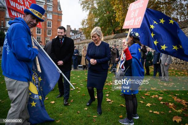 Leader of the Social Democratic and Labour Party Colum Eastwood and Vice President of Sinn Fein Michelle O'Neill walk between anti-Brexit protesters...