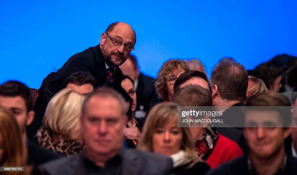 Leader of the Social Democratic Party (SPD) Martin Schulz speaks to an unidentified delegate during the last day of the SPD party congress on December 9, 2017 in Berlin. Germany's Social Democrats, the country's second strongest party, agreed to kick off exploratory talks with Chancellor Angela Merkel's conservatives that could lead to a new coalition government early next year. / AFP PHOTO / John MACDOUGALL