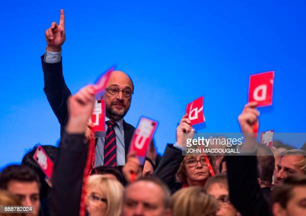 Leader of the Social Democratic Party Martin Schulz votes by a show of hands on the last day of the SPD party congress on December 9 2017 in Berlin...