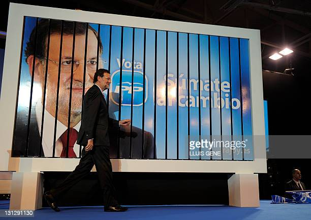 Leader of the Spanish opposition party Partido Popular and candidate for general elections, Mariano Rajoy walks in front of an election poster during...