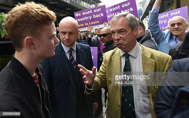 Leader of the United Kingdom Independence Party Nigel Farage gestures as he is confronted by Luke Holland whilst campaigning to leave the European...