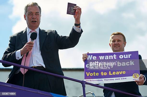 Leader of the United Kingdom Independence Party Nigel Farage holds aloft a British Passport as he addresses supporters from his party's opentop bus...