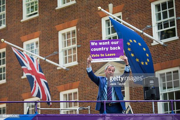 Leader of the United Kingdom Independence Party Nigel Farage poses with a placard on top of a campaign bus parked outside Europe House in Westminster...