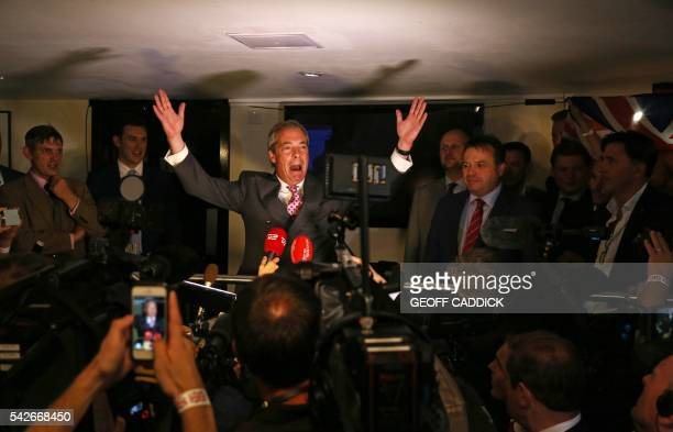 Leader of the United Kingdom Independence Party Nigel Farage reacts watched by British businessman Arron Banks at the LeaveEU referendum party at...