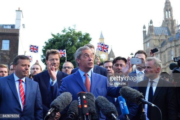 Leader of the United Kingdom Independence Party Nigel Farage watch by British businessman Arron Banks speaks during a press conference near the...