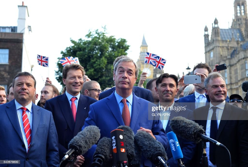 Leader of the United Kingdom Independence Party (UKIP), Nigel Farage (C), watch by British businessman Arron Banks (L), speaks during a press conference near the Houses of Parliament in central London on June 24, 2016. - Britain has voted to leave the European Union by 51.9 percent to 48.1 percent, final results from all 382 of Britain's local counting centres showed on Friday.