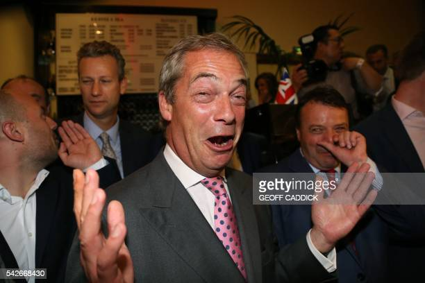 Leader of the United Kingdom Independence Party Nigel Farage watched British businessman Arron Banks reacts at the LeaveEU referendum party at...