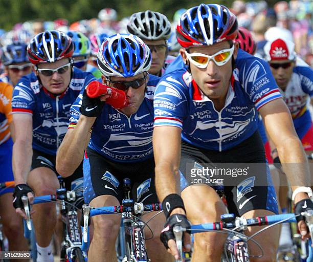 leader of the US Postal Service team US Lance Armstrong drinks as he rides surrounded with his teammates and compatriots Floyd Landis and George...