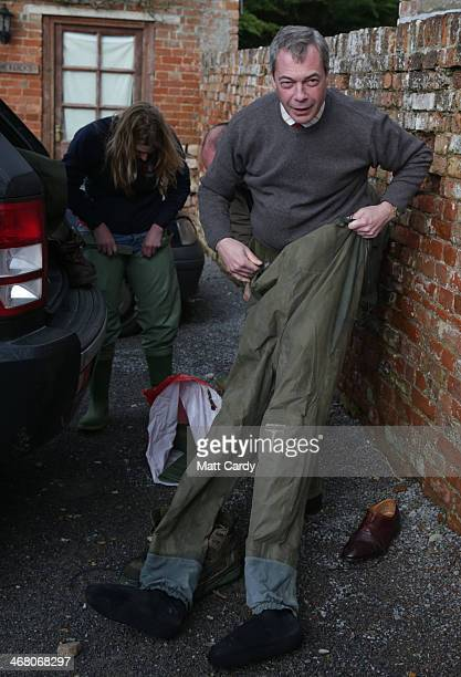 Leader of UKIP Nigel Farage gets into his waders as he visits at Burrowbridge on the Somerset Levels on February 9, 2014 near Bridgwater, England....