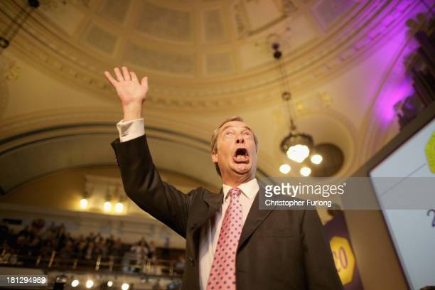 Leader of UKIP Nigel Farage takes the applause after addressing delegates during his keynote speech on September 20 2013 in London England Members of...
