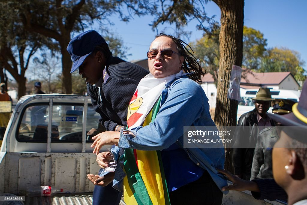 Leader of Women of Zimbabwe Arise (WOZA) Jenni Williams (R) scuffles with a female police officer while being arrested on August 6 2016, after picketing outside Queens Sports Grounds during a match between Zimbabwe and New Zealand in Bulawayo, to demand the abolishment of bond notes that the government plans to introduce. Zimbabwe has been hit by a series of street protests - the largest seen in many years in the country, triggered by an economic crisis that has left banks short of cash and the government struggling to pay its workers. / AFP / ZINYANGE