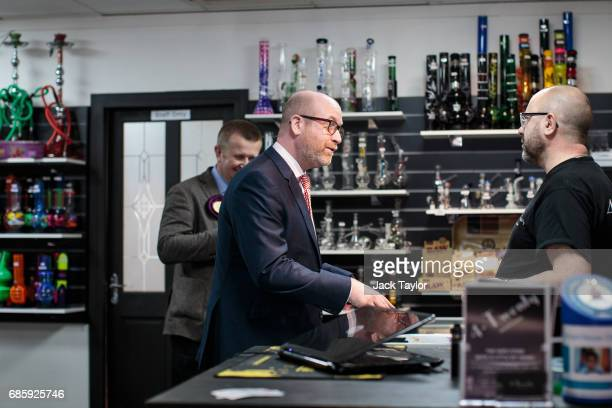 Leader Paul Nuttall speaks to a worker in a smoke and vape shop as he campaigns on May 20 2017 in Elm Park England All political parties continue to...