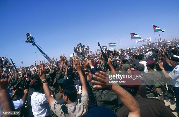 PLO leader Yasser Arafat greets hundreds of supporters during his homecoming to Gaza