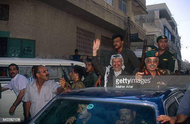 PLO leader Yasser Arafat protected by armed bodyguards greets hundreds of supporters during his homecoming to Gaza
