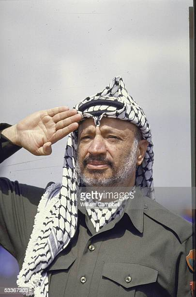 Leader Yasser Arafat saluting upon arriving for the OAU meeting.