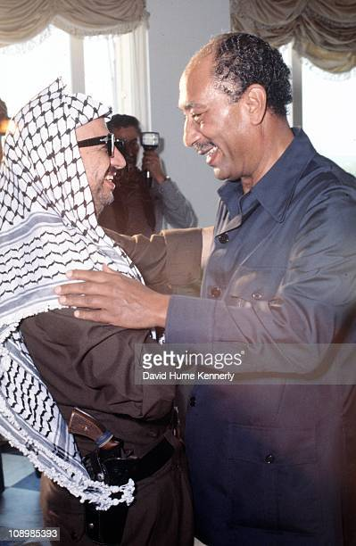 PLO leader Yasser Arafat smiles while embracing Egyptian president Anwar al Sadat Alexandria Egypt July 1977 Arafat visited Sadat to mediate a border...