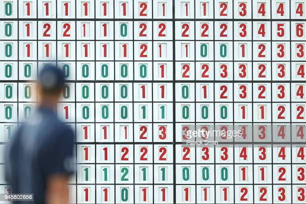 A leaderboard is seen behind Jordan Spieth of the United States on the 17th green during the first round of the 2018 Masters Tournament at Augusta...