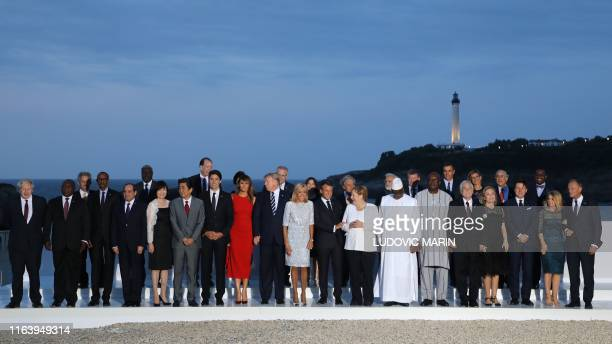 G7 leaders and guests pose for a family picture with the Biarritz lighthouse in the background on the second day of the annual G7 summit in Biarritz...