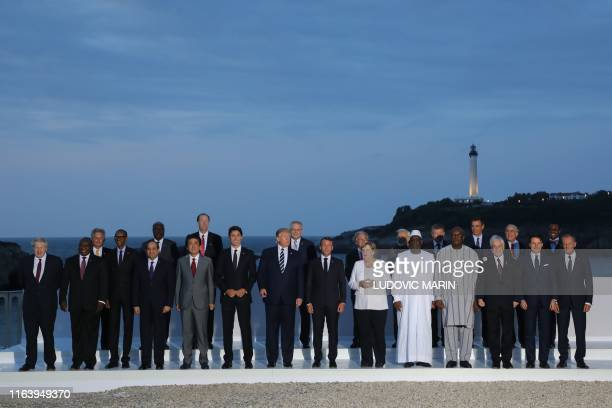 Leaders and guests pose for a family picture with the Biarritz lighthouse in the background on the second day of the annual G7 summit in Biarritz,...