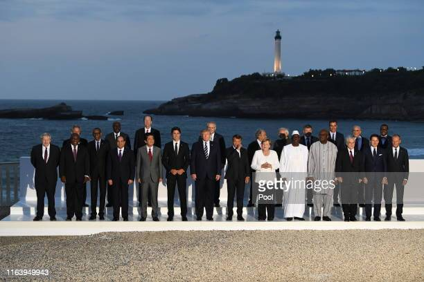 G7 leaders and guests pose for a family picture with the Biarritz lighthouse in the background on the second day of the annual G7 summit LR Britain's...
