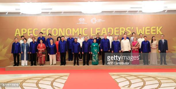 Leaders and their spouses pose for a family photo ahead of the AsiaPacific Economic Cooperation Summit leaders gala dinner in the central Vietnamese...