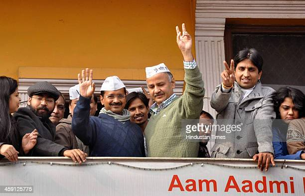 AAP leaders Arvind Kejriwal Manish Sisodia and Kumar Vishwas wave to public before press conference at its Kaushambi office on December 23 2013 in...