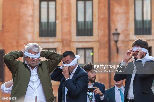 Leaders Five Star Movement Beppe Grillo Luigi Di Maio and Alessandro Di Battista cover their eyes with a white scraf during the demonstration by the...