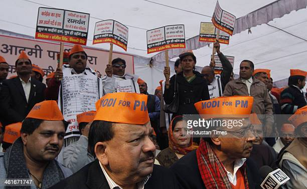BJP leaders Harshvardhan and Vijay Goel wearing saffron caps with the slogan Modi for PM during protest against ruling AAPs alleged failure to...