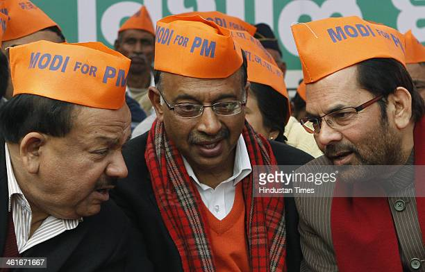 BJP leaders Harshvardhan Vijay Goel and Mukhtar Abbas Naqvi wearing saffron caps with the slogan Modi for PM during protest against ruling AAPs...