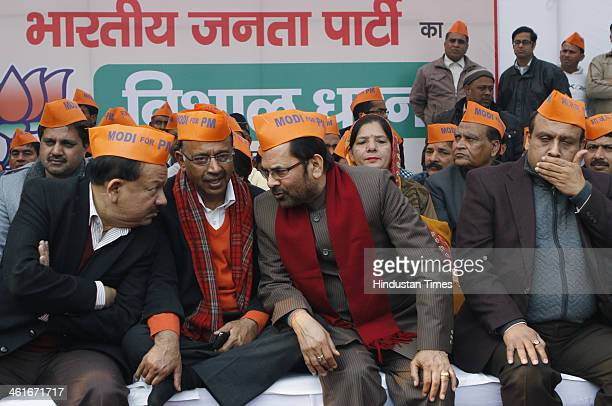 BJP leaders Harshvardhan Vijay Goel Mukhtar Abbas Naqvi and Vijendra Gupta wearing saffron caps with the slogan Modi for PM during protest against...