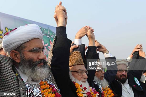 Leaders of JammateIslami Siraj ulHaq Qazi Hussain Ahmed Syed Munawar Hassan and Shabir Ahmed raise hands during a rally in Peshawar on December 18...