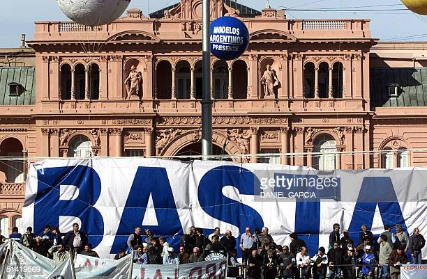 Leaders of labour unions take part in a protest with a giant banner reading 'Basta' before the presidential palace 29 August 2001 in Buenos Aires Two...